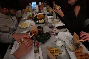 Tafel vol voedsel met mensenhanden