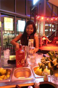 Een jonge dame achter een tafel vol cocktail spullen