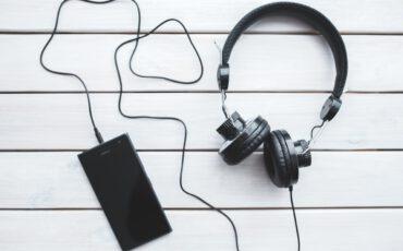 Een zwarte mobiele telefoon die is aangesloten aan een zwarte koptelefoon op een witte houte achtergrond